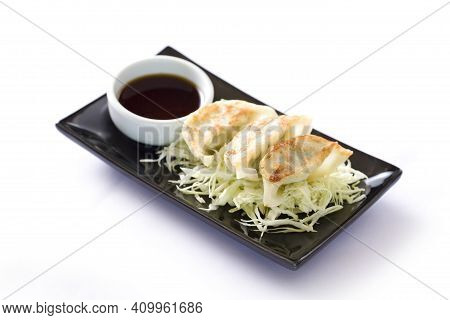 Fried Asian Dumplings Gyozas Potstickers In Black Ceramic Plate Served With Bowl Of Soy Onion Sauce