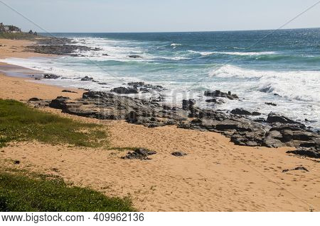 Dune Covered With Vegetation And Black Rocks In Sea