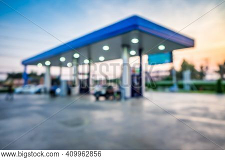 Abstract Blur Photo Of Car Refueling On Gas Station At Sunset. Pump Gasoline Gauge Oil In The Evenin