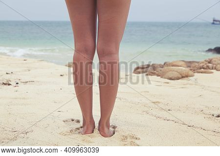Back View Of Beauty Woman Waxed Legs Standing On The Beach.