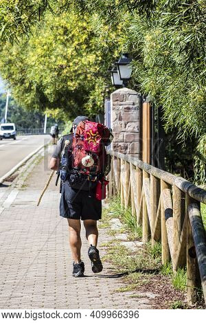 Pilgrim Walking Towards San Vicente De La Barquera. Way Of St. James, Cantabria, Spain. Man Backpack