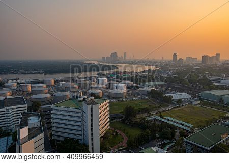 Aerial View Of The Modern Buildings And Oil Refinery Fuel Tank At Sunset With Chao Phraya River, Ban