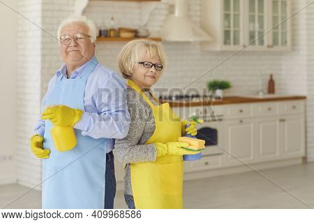 Ederly Couple Holding Cleaning Detergents And Standing With Their Backs To Each Other In The Kitchen
