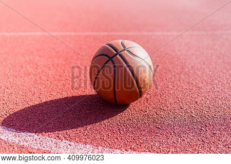 Orange Ball For Basketball Lying On The Sport Court.sport Red Court Outdoor.