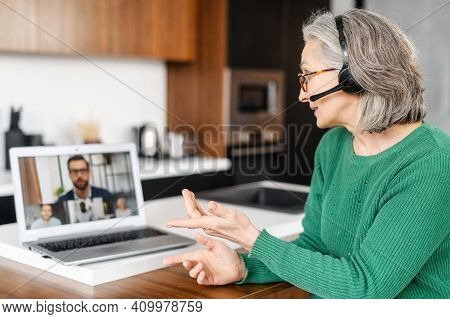 Strict Aged Entrepreneur Sitting At The Laptop At Home With Headset, Remote Guidance, Explaining, Ho