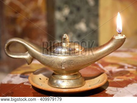 Ancient Golden Oil Lamp With Flame To Evoke The Genie Of The Lamp