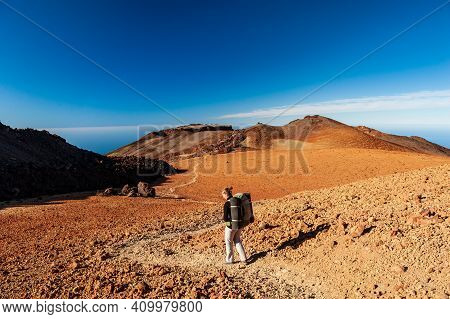 Young Woman Hiker With Backpack Trekking Near Pico Del Teide Mountain In El Teide National Park. Ten