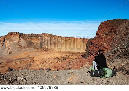Young Woman Hiker With Backpack Sitting And Looking At  Desert Near Pico Del Teide Mountain In El Te