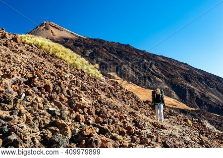 Young Woman Hiker With Backpack Descending From Pico Del Teide Mountain In El Teide National Park. T