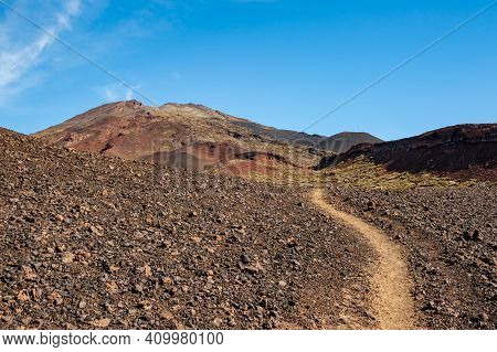Path In Desert And Silhouette Of Volcano Del Teide Against  Blue Sky And Female Hiker With Backpack.