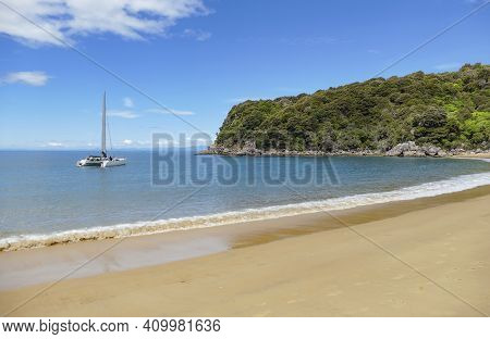 Coastal Sunny Scenery With Catamaran At The Abel Tasman National Park In New Zealand
