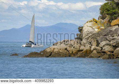 Coastal Sunny Scenery Including A Catamaran At The Abel Tasman National Park In New Zealand