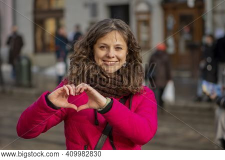 Street Portrait Of A Cheerful, Successful Middle-aged Woman Who Folded Her Hands In The Shape Of A H