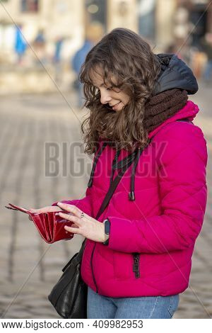 Street Portrait Of A Cheerful Woman 30-35 Years Old With Curly Hair And Delicate Features Against Th