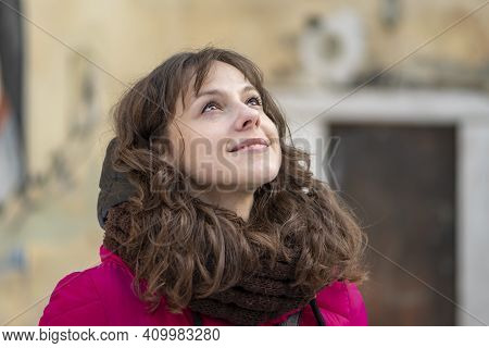Street Portrait Of A Cheerful Woman 30-35 Years Old With Curly Hair And Delicate Features On The Bac