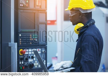 Worker Man With Yellow Helmet And Ear Protection Typing Keyboard Of Laptop Computer At Factory