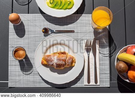 Topview Of A Breakfast Setup With A Croissant On Top Of A Plate, Some Fruit On The Side, Orange Juic