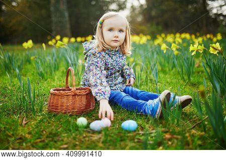 Three Year Old Girl Playing Egg Hunt On Easter. Child Sitting On The Grass With Many Narcissi And Ga