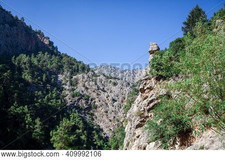 Rock Mountain Cliff With Green Grass And Trees Under Blue Sky. Lonely Mountain Pick Over The Cliff