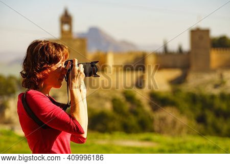 Mature Female Tourist With Camera Taking Travel Photos In Antequera City, Alcazaba Fortress In The D