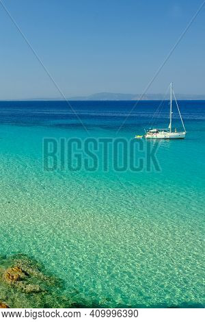 Chalkidiki, Greece - August 14, 2017 : A Single Sailboat In The Turquoise Waters Of Chalkidiki Greec