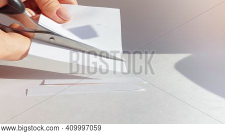 A Womans Hand Cuts A Sheet Of White Paper With Scissors And Cuts Off The Corners. Close-up, Diy Conc