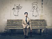 Businessman sitting on a bench with an angel and a devil on his sides poster