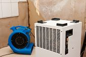 Elimination of water damage with dryer and fan. poster