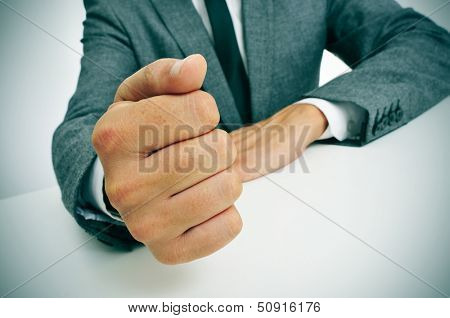 man wearing a suit banging his fist on the desk
