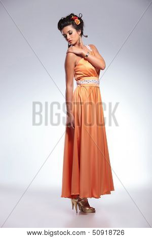 full length portrait of a young fashion woman holding her hand on her shoulder and looking over it, away from the camera. on gray background