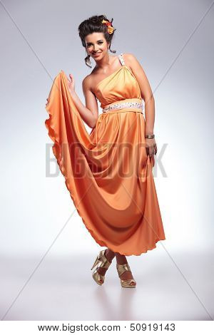 full length photo of a young fashion woman holding up her dress with one hand while standing with her legs crossed and smiling for the camera. on gray background