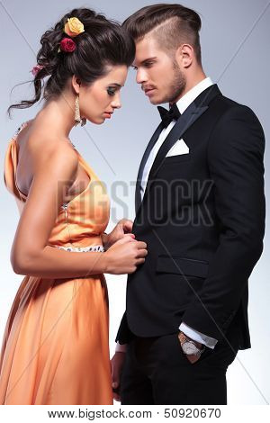 young fashion couple with woman undressing man while he looks at her. on gray background
