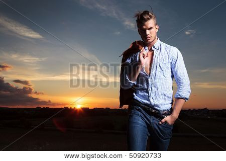 casual young man standing with a hand in his pocket outdoor during sunset