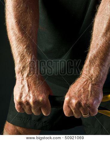 man's hands holding tennis racket