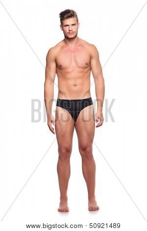 full length portrait of a young man wearing nothing but his underware and looking at the camera, isolated on white