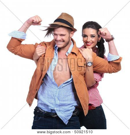 young casual couple smiling while man shows his biceps and woman holds him by his shoulders from behind and smiles for the camera. on white background