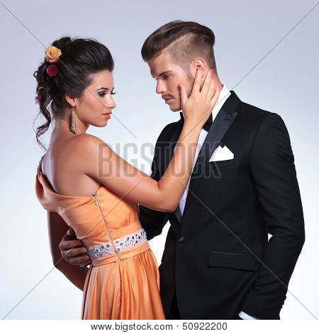 young fashion couple with woman caressing the man's face while looking at eachother. on gray background