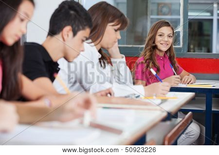 Portrait of teenage schoolgirl sitting at desk with friends writing in foreground