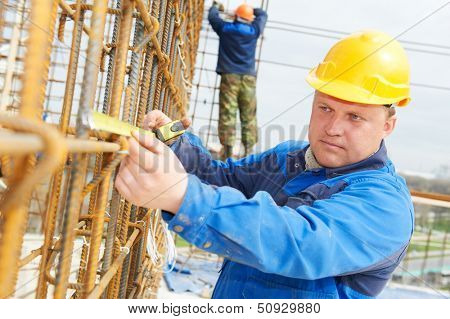 builder worker measuring metal rods bars into framework reinforcement for concrete pouring at construction site