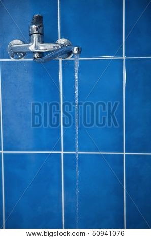 water tap with flower water against a blue ceramic tile