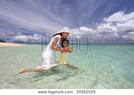 Mother and child playing at the beach
