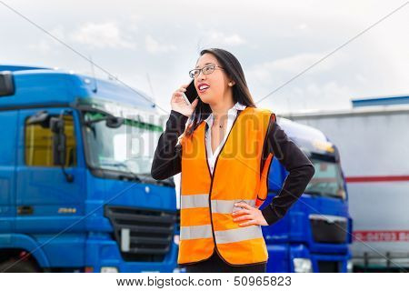 Logistics - female Asian forwarder or supervisor with mobile phone, in front of trucks and trailers, on transshipment point