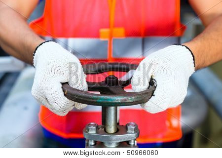 Two technicians or engineers working on a valve on building technical equipment or industrial site or factory