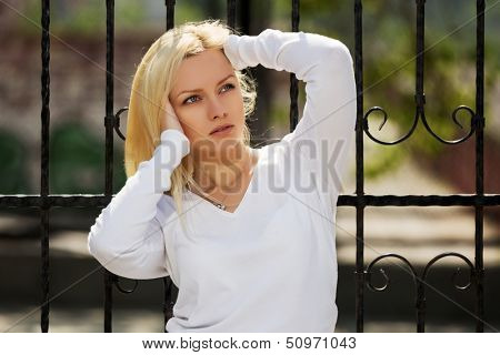 Blond woman at the cast iron fence