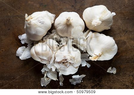 Garlic bulbs on a old kitchen table, shot from above. Peeling white skin.