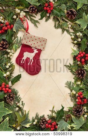 Christmas eve border with red reindeer stocking, holly, ivy and mistletoe over old parchment paper. poster
