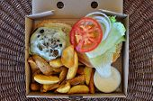 Burger with fries and melted cheese mushrooms. Takeaway food in packaging. poster