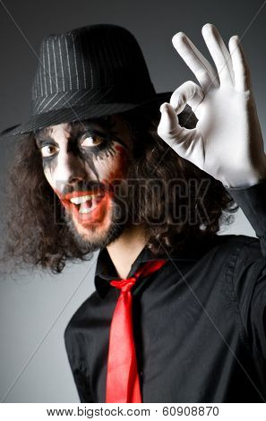 Joker personification with man in dark room