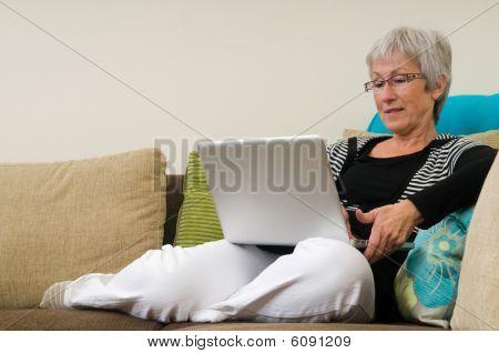 Senior weiblich working auf einem Laptop, entspannt auf der couch