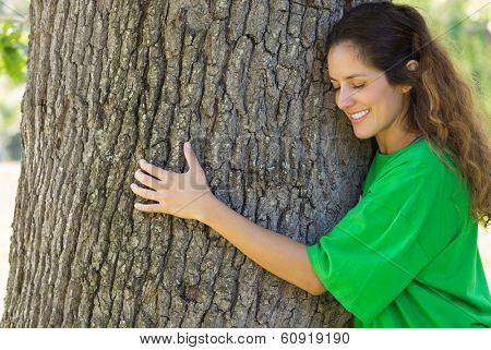 Smiling female environmentalist hugging tree trunk in park